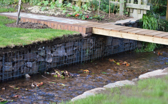 Garden project reclaiming lawn and elegantly restraining small river
